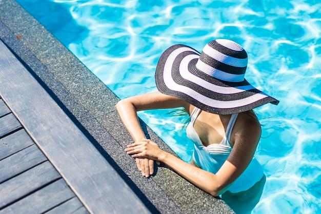 Bella giovane donna asiatica con cappello in piscina per viaggi e vacanze Foto Gratuite