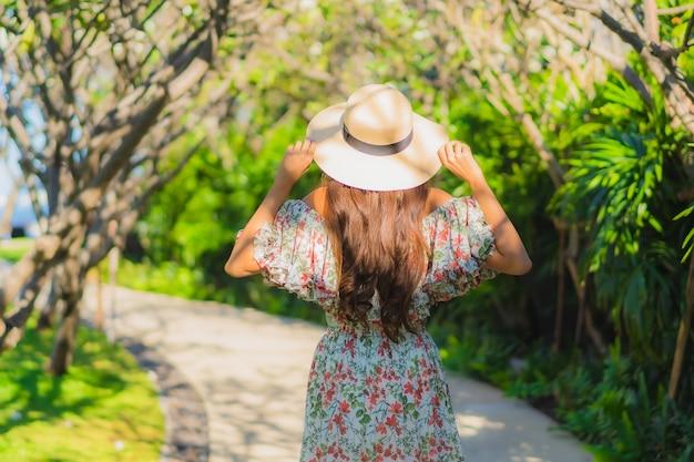 Bella giovane donna asiatica del ritratto che cammina con felice intorno alla vista all'aperto del giardino Foto Gratuite
