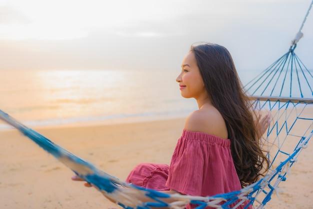 Bella giovane donna asiatica del ritratto che si siede sull'amaca con il mare ed il oce felici vicini della spiaggia di sorriso Foto Gratuite