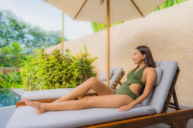 Bella giovane donna asiatica del ritratto che si siede sulla piattaforma della sedia con la piscina neary dell'ombrello Foto Gratuite