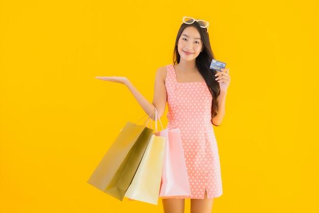 Bella giovane donna asiatica del ritratto con il sacchetto della spesa variopinto con la carta di credito Foto Gratuite
