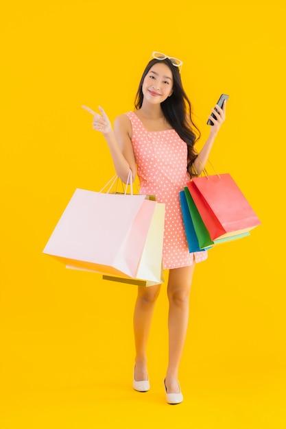 Bella giovane donna asiatica del ritratto con il sacchetto della spesa variopinto con lo smartphone Foto Gratuite