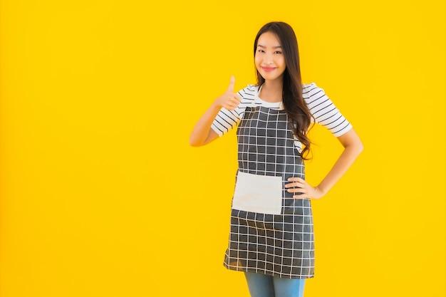 Bella giovane donna asiatica del ritratto con il sorriso del grembiule felice Foto Gratuite