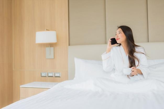 Bella giovane donna asiatica del ritratto con il telefono cellulare astuto in camera da letto Foto Gratuite