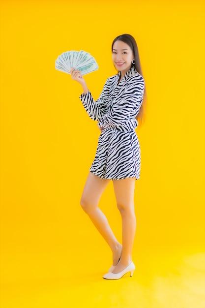 Bella giovane donna asiatica del ritratto con molti contanti e soldi su giallo Foto Gratuite