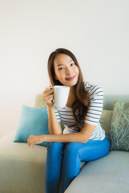 Bella giovane donna asiatica del ritratto sul sofà con la tazza di caffè Foto Gratuite