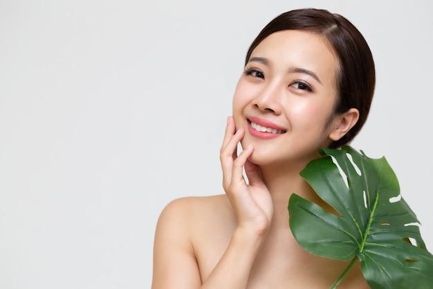 Bella giovane donna asiatica felice con pelle fresca pulita e foglie verdi, cura del viso di bellezza della ragazza, trattamento facciale e concetto della stazione termale di cosmetologia Foto Premium