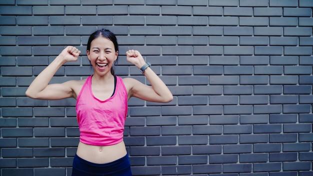 Bella giovane donna asiatica sana del corridore che ritiene sorridere felice e che guarda alla macchina fotografica dopo avere corso Foto Gratuite