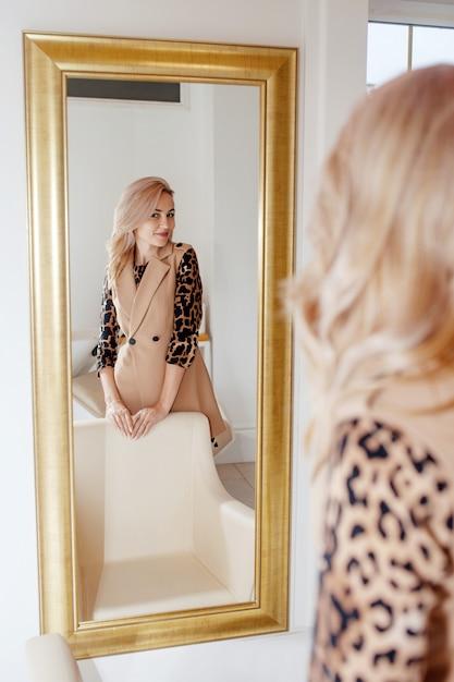 Bella giovane donna astuta che sta davanti ad uno specchio. ragazza sorridente caucasica che esamina riflessione in specchio Foto Premium