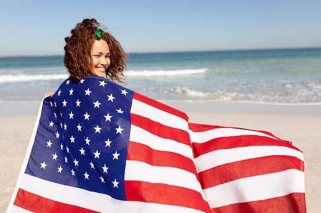 Bella giovane donna avvolta in bandiera americana che guarda l'obbiettivo sulla spiaggia al sole Foto Gratuite