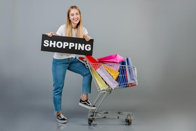Bella giovane donna bionda con il segno di acquisto e carrello con i sacchetti della spesa variopinti isolati sopra grey Foto Premium