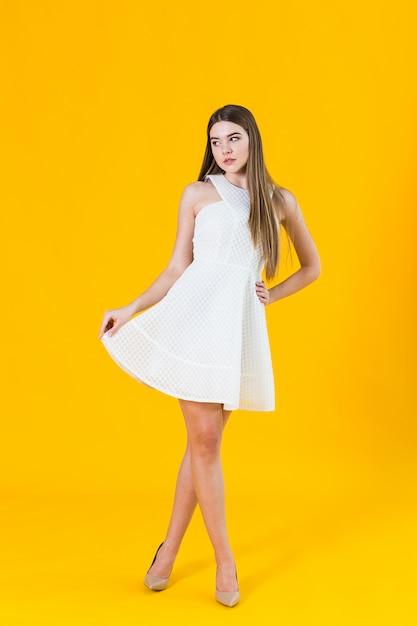 Bella giovane donna bionda in vestito piacevole dalla molla, posante sul fondo giallo in studio Foto Premium
