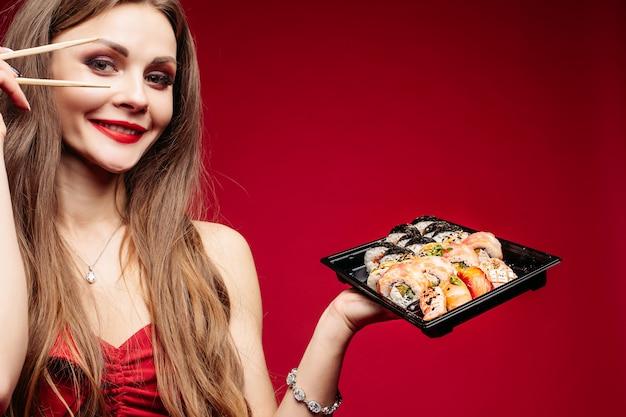 Bella giovane donna castana con la scatola di sushi e bastoni su rosso. Foto Premium