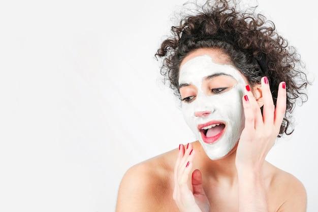 Bella giovane donna che applica maschera facciale sul suo viso isolato su sfondo bianco Foto Gratuite