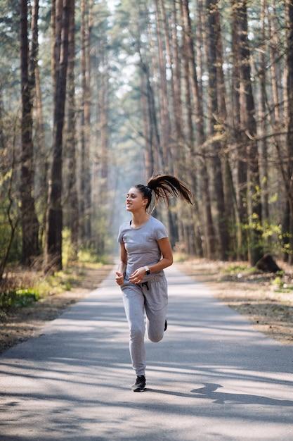 Bella giovane donna che funziona nel parco verde il giorno di estate soleggiato Foto Gratuite