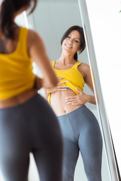 Bella giovane donna che guarda se stessa riflessione nello specchio a casa. Foto Gratuite