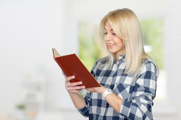 Bella giovane donna che legge e che tiene un libro Foto Premium