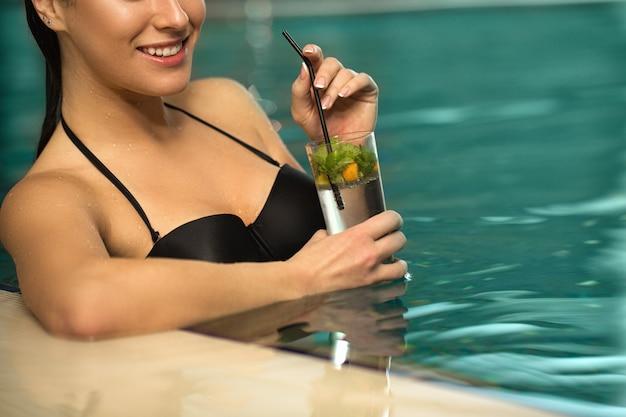 Bella giovane donna che nuota in piscina al centro benessere Foto Premium