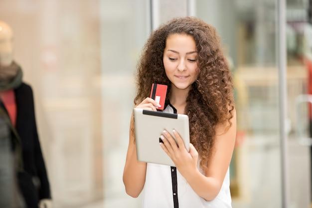 Bella giovane donna che paga con carta di credito per lo shopping Foto Gratuite