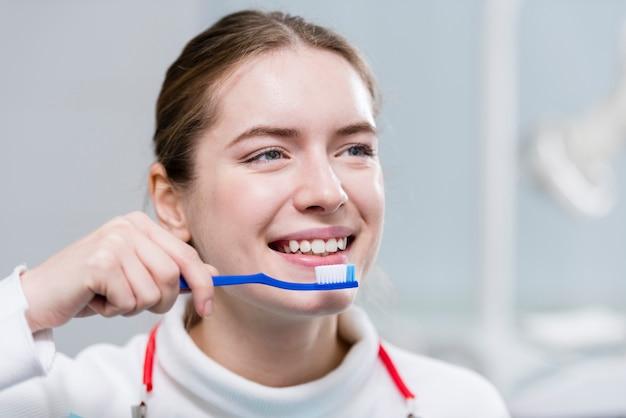 Bella giovane donna che pulisce i suoi denti Foto Gratuite
