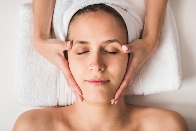 Bella giovane donna che riceve il massaggio facciale con gli occhi chiusi in un salone spa Foto Gratuite