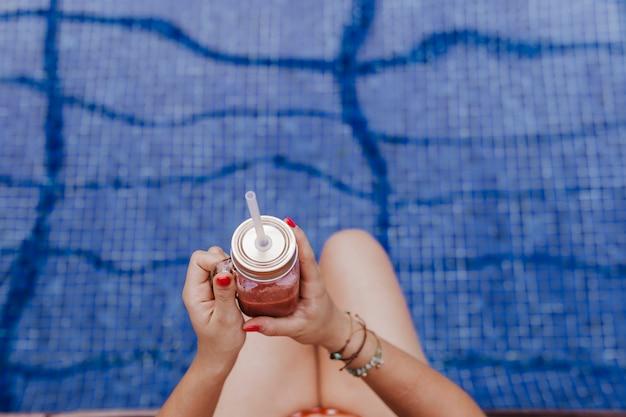 Bella giovane donna che si rilassa allo stagno. tenendo un succo sano e rilassante estate e stile di vita. vista dall'alto Foto Premium