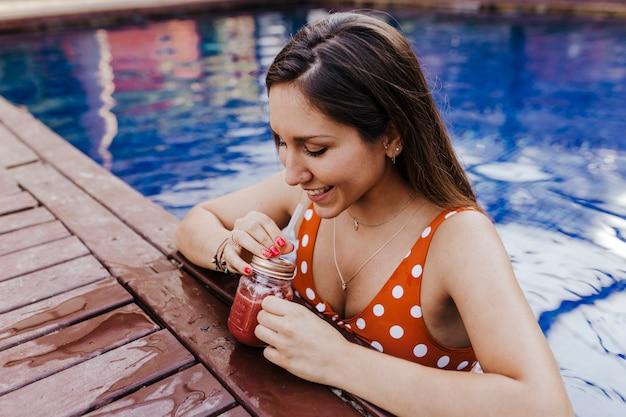 Bella giovane donna che si rilassa allo stagno. tenendo un succo sano e rilassante estate e stile di vita Foto Premium