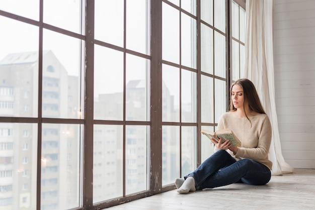 Bella giovane donna che si siede vicino al libro di lettura della finestra di vetro Foto Gratuite