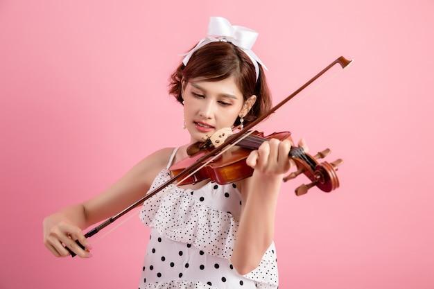 Bella giovane donna che suona il violino sopra il rosa Foto Gratuite