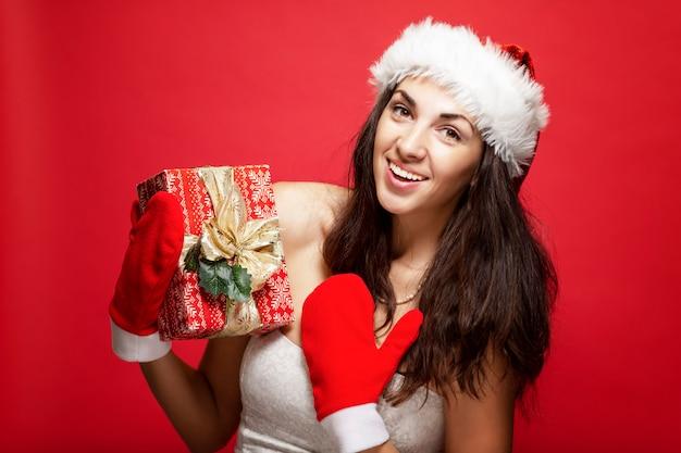 Bella giovane donna con cappello e guanti di babbo natale con un regalo in mano sorridendo. racconto di natale. cartolina. verticale. rosso Foto Premium