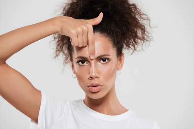 Bella giovane donna con i capelli ricci con l'indice Foto Gratuite