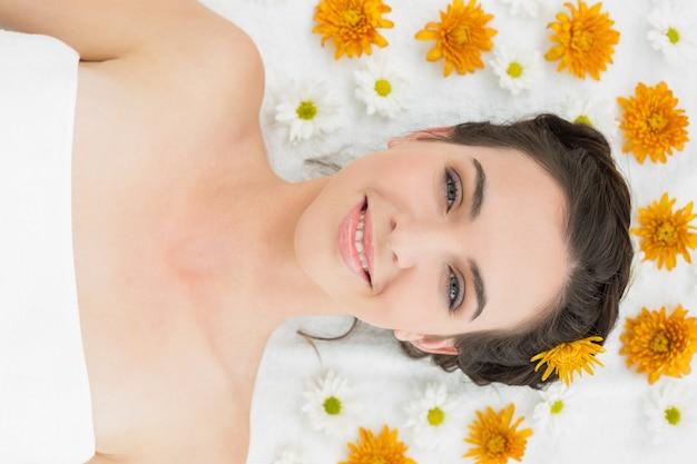 Bella giovane donna con i fiori nel salone di bellezza Foto Premium