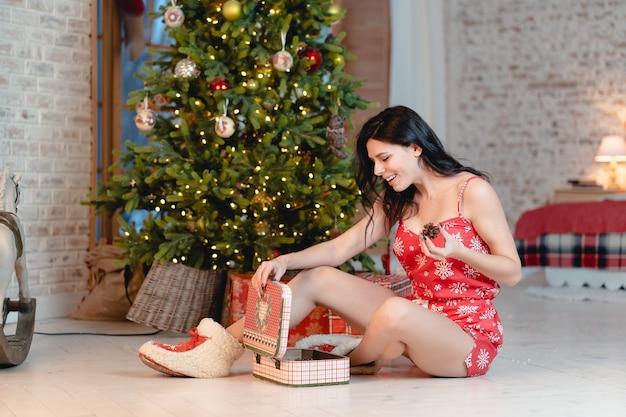 Bella giovane donna con i regali sull'albero di natale Foto Gratuite