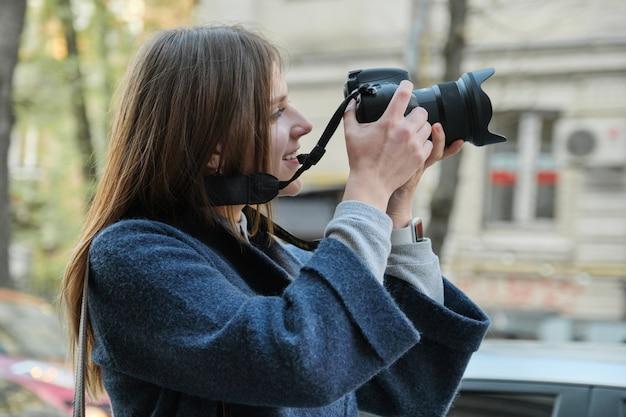 Bella giovane donna con la macchina fotografica in città. Foto Premium
