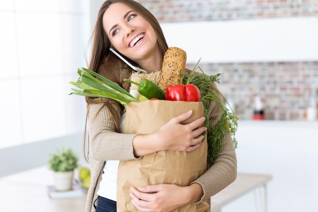 Bella giovane donna con le verdure nel sacchetto di drogheria a casa. Foto Gratuite