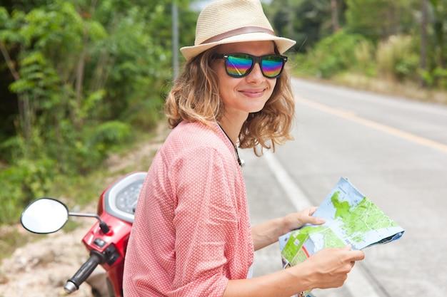 Bella giovane donna con mappa in mano e una moto sulla strada. viaggi, navigazione, turismo Foto Premium