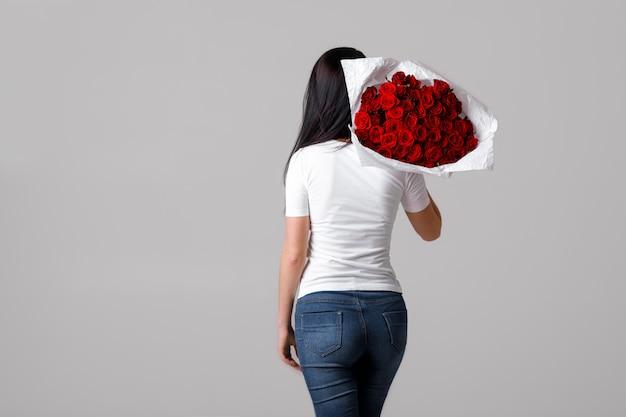 Bella giovane donna con un grande mazzo di rose rosse Foto Premium