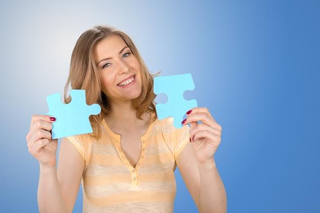 Bella giovane donna d'affari in possesso di un pezzo di puzzle blu Foto Premium