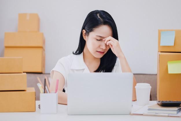 Bella giovane donna di affari asiatica sensazione emicrania e stress nello spazio ufficio con scatola del prodotto. Foto Premium