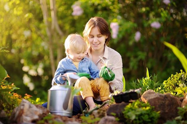 Bella giovane donna e il suo figlio carino piantare piantine a letto nel giardino domestico al giorno di estate Foto Premium