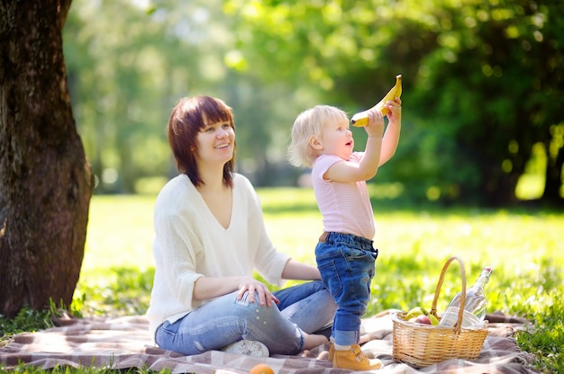Bella giovane donna e il suo piccolo figlio adorabile con un picnic nel parco soleggiato Foto Premium