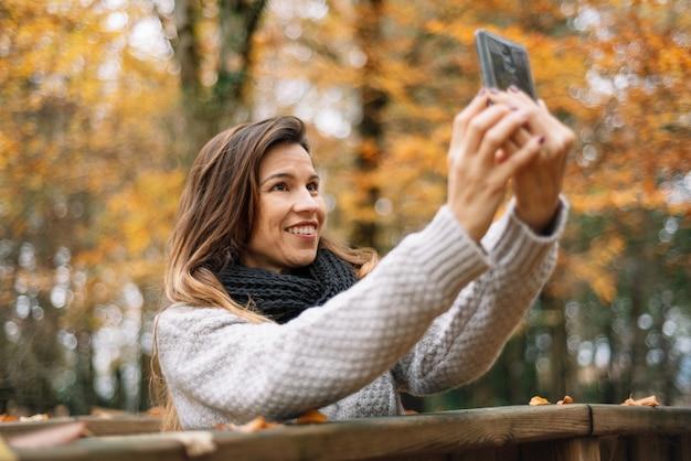 Bella giovane donna felice che prende selfie con lo smartphone nel parco di autunno. concetto di stagione, tecnologia e persone. Foto Premium
