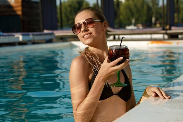 Bella giovane donna felice che si rilassa nella piscina Foto Premium