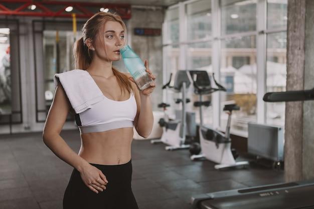 Bella giovane donna fitness allenandovi in palestra Foto Premium