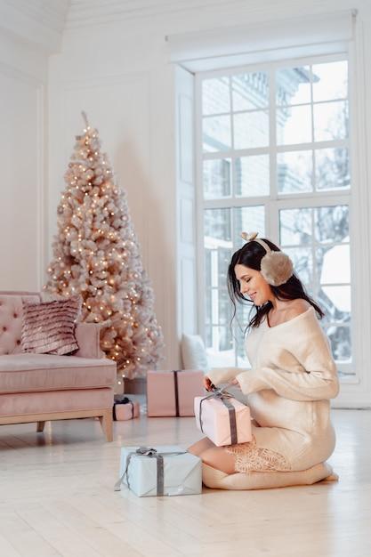Bella giovane donna in abito bianco in posa con scatole regalo Foto Gratuite