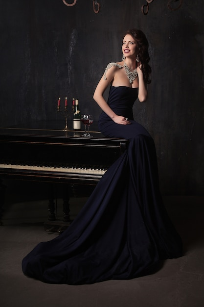 Bella giovane donna in abito nero accanto a un pianoforte con candele candelabri e vino, atmosfera drammatica scuro del castello. boemia. Foto Premium