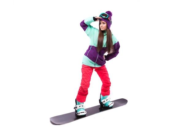 Bella giovane donna in tuta da sci viola cavalca snowboard nero Foto Premium