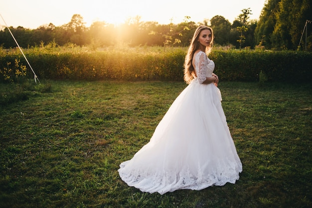 Bella giovane donna in un abito da sposa bianco e stivali neri al tramonto. Foto Premium