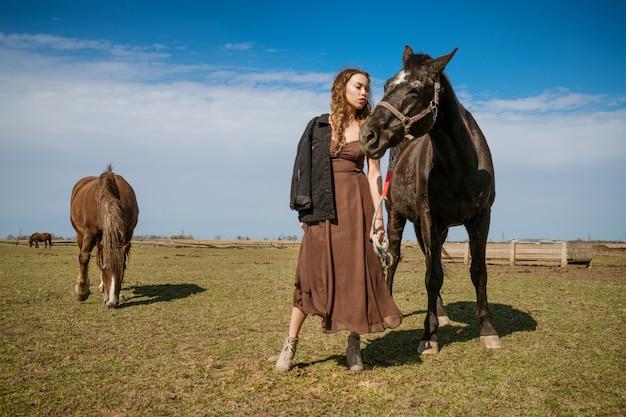 Bella giovane donna in un campo con i cavalli. modella attraente. Foto Premium