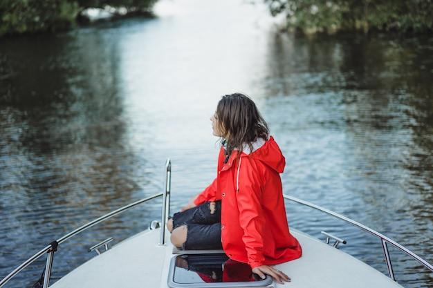 Bella giovane donna in un impermeabile rosso cavalca uno yacht privato. stoccolma, svezia Foto Gratuite